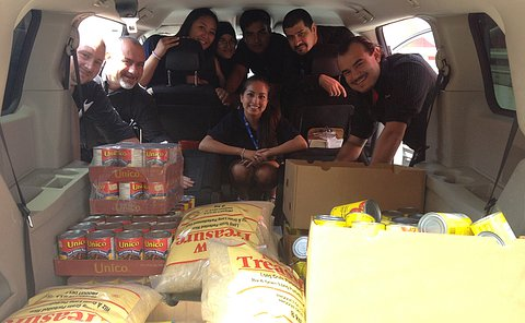 A group of people in a min-van filled with food