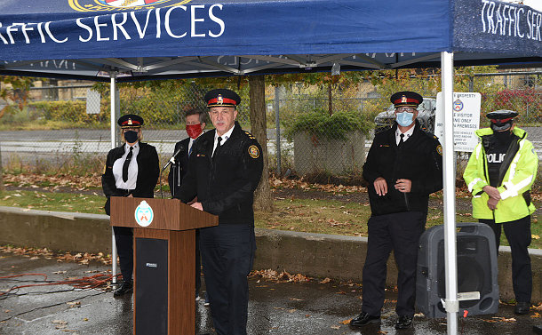 A group of men and women in police uniforms standing under a tent, with one man in front of a podium speaking.