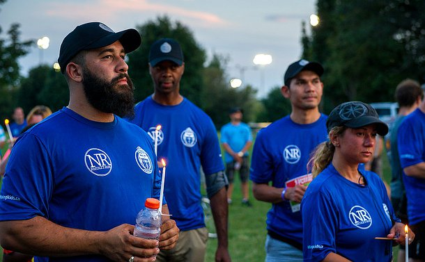 A man with a beard wearing a Nicole's Run tshirt with a candle in his hand, around him other people also hold candles.