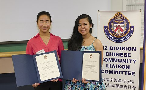 Two teenage girls holding certificates