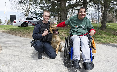 A man in TPS uniform and German Shepherd police dog being pet by a man in a wheelchair