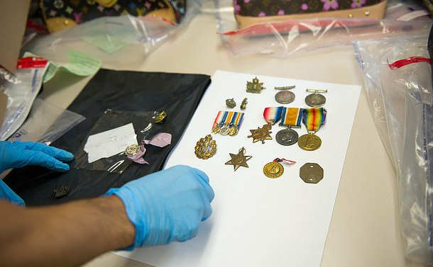 A man's hands in blue gloves as he places WWI medals on a table