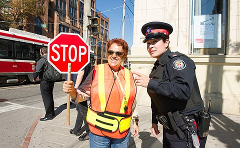 A woman in TPS uniform pointing beside another woman in an orange safety vest and holding up a stop sign