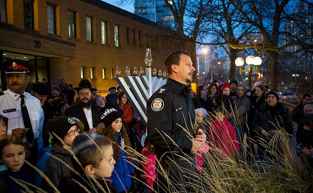 A man in TPS uniform wearing a yamaka near a large menorah and a group of people