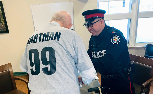 A man wearing a Bartman 99 T-shirt accepting a gift from a man in TPS uniform