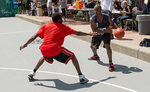 A Toronto Police team member in blue uniform with the basketball in his hand runs faces off against a member of the opposing team.