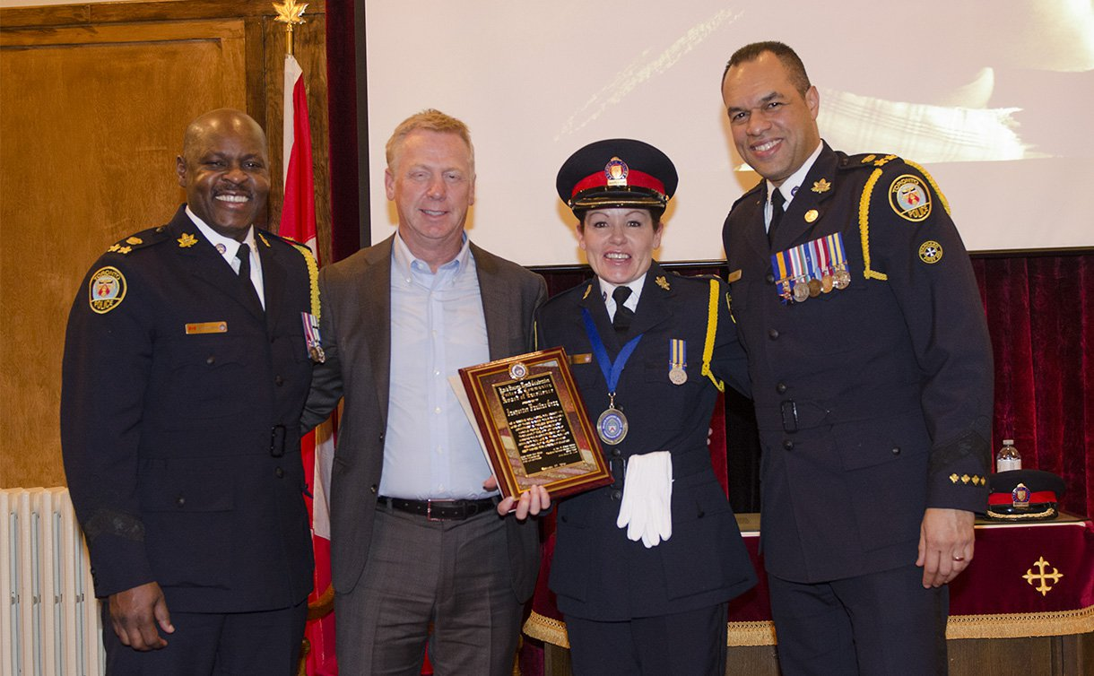 Two men and one woman in TPS uniform holding a plaque, with another man