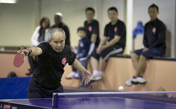 A man holds a paddle as a ball travels over a table tennis net
