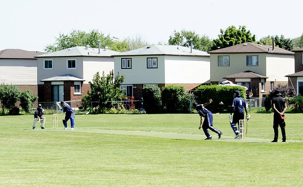 A man bowls a cricket ball as a batsman and player wait for the ball