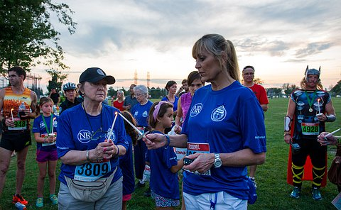 Two woman wearing blue tshirts that say NR are holding candles, one is lighting the candle for the other one, they are outdoors in a park and it is evening.