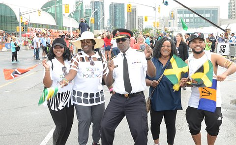 A man in TPS uniform dances with a group of people