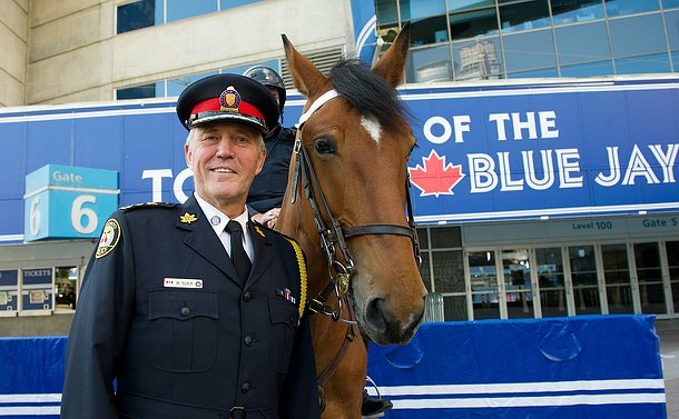 Chief of Police standing next to a brown horse.