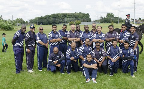 A group of men in cricket uniform in several rows