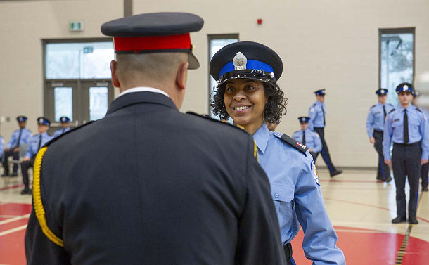 A woman in TPS special constable uniform in front of a man in police uniform