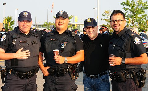 Three men in TPS uniform with another man