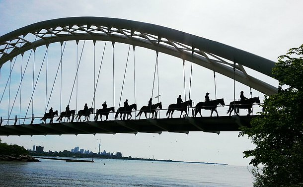 A line of officers on horseback in silhouette on a foot bridge from low angle