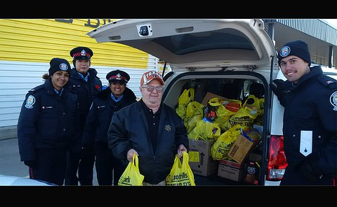 A man holding grocery bags beside men and women in TPS Auxiliary uniform beside a trunk full of food