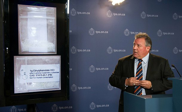 A man stands at a podium beside a TV monitor showing plastic resealable bags containing white crystals