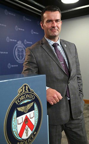 A man leaning against a podium with the TPS crest on it