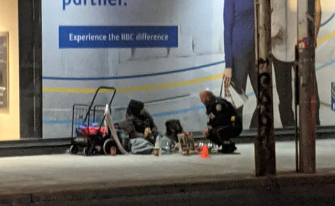 A man in TPS uniform crouches beside a person