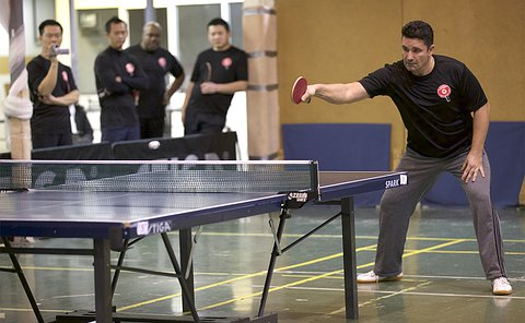 A man playing table tennis with others in background