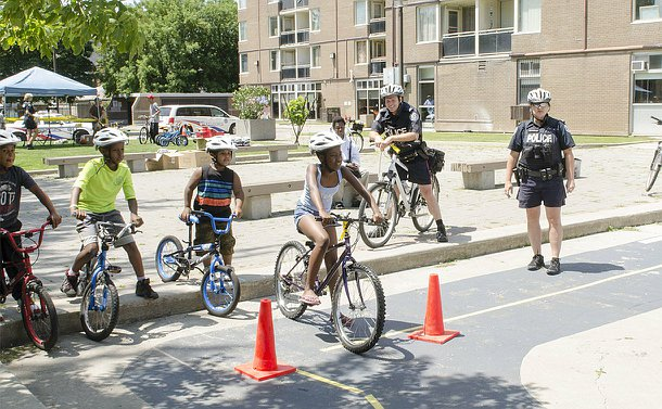 Children in a line on their bicycles looking ahead while two officers, also on bicycles, stand to the side watching.
