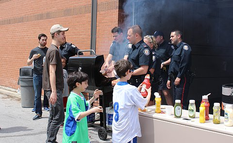 A group of TPS officers around a BBQ as other people hold hot dogs
