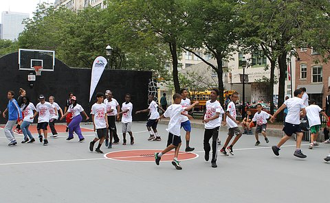 A large group of children running on an outdoor basketball court