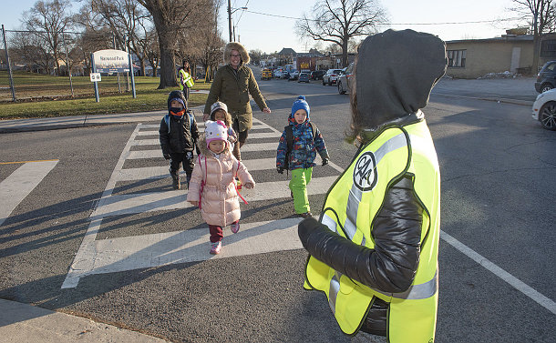 A group of kids and adult crossing the street between two kids in yellow vests