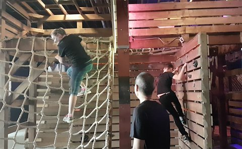 A woman and a boy climb ropes in an obstacle course