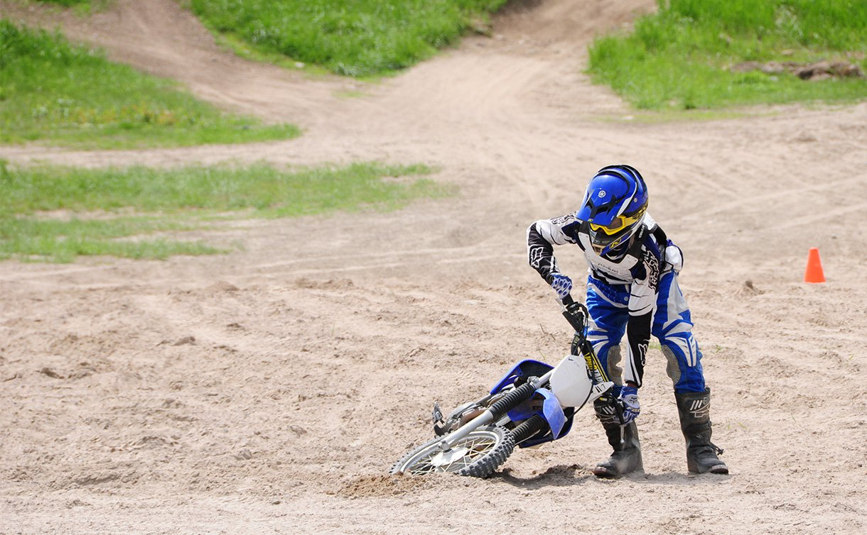 A boy wearing protective helmet and gear picks up a dirt bike from the sand
