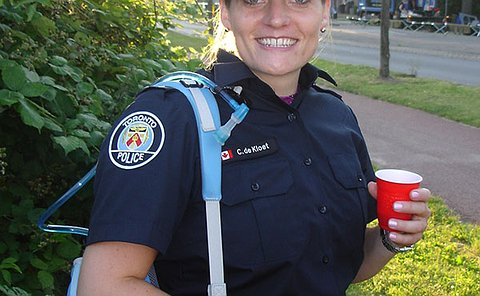 A woman smiling, dressed in the police uniform wearing a backpack over her shoulder