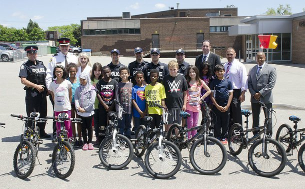 A group of men and women in TPS uniform standing alongside other adults and children behind a row of bicycles in a school playground