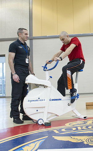 A man on a stationary bike beside another man in a gym