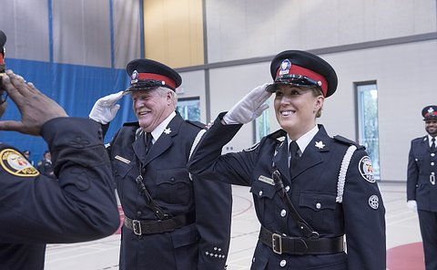 A man and woman in TPS uniform smiling and saluting