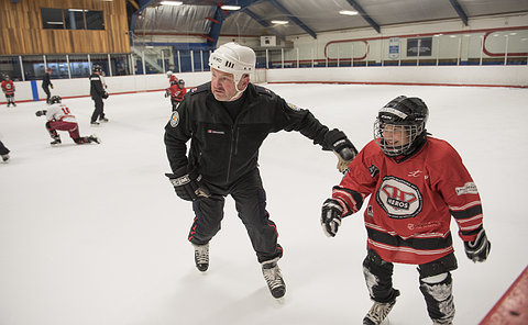 A man in TPS uniform with a girl in hockey uniform on a rink