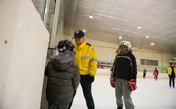 An officer in a yellow CRU jacket and skates stands in a ice rink talking to 2 children.