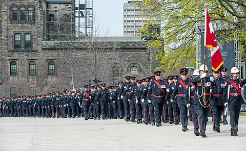 a long line of officers marching in uniform.