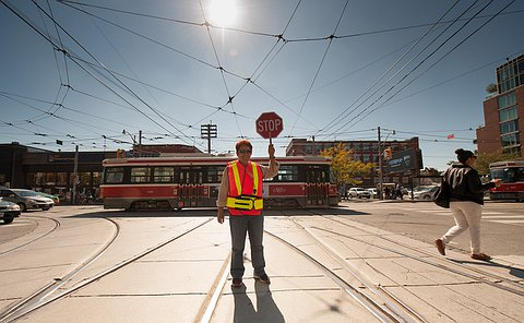 A woman wearing a safety vest holds up a stop sign as a person walks by and a streetcar passes behind her
