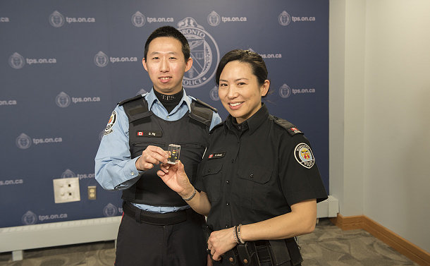 A man in TPS auxiliary uniform and a woman in TPS uniform holding a Lego figure