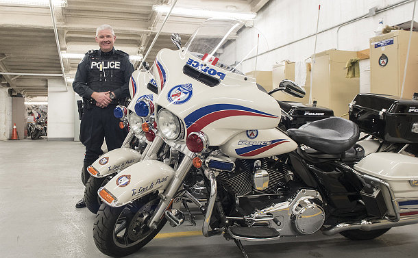 A man in TPS uniform standing amongst a row of TPS motorcycles