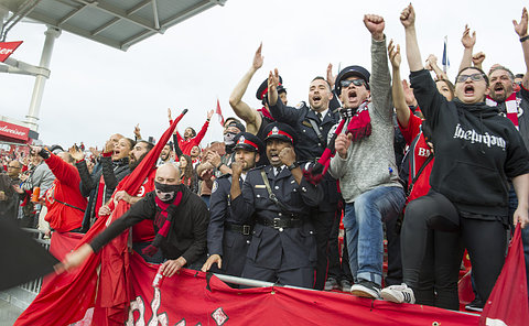 Three men in TPS uniform in a crowd of TFC fans