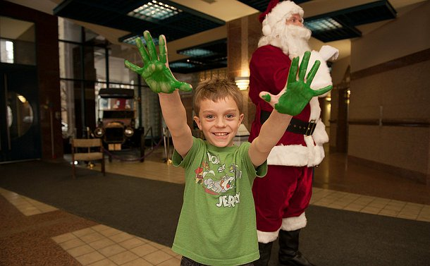 A boy with palms painted green throws them up in the air as he smiles.