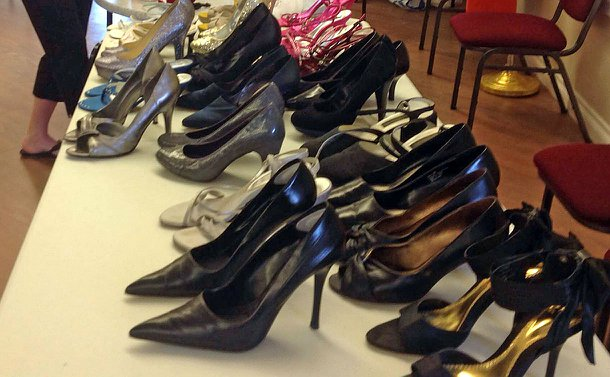 A table, setup with a selection of women's high-heel dress shoes