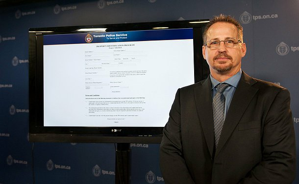 A man stands in front of a TV screen with a TPS website on display