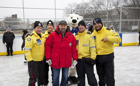 A man and a bear mascot stand with men in TPS uniform on an outdoor ice rink