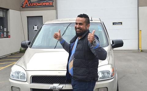 A man giving thumbs up beside a minivan