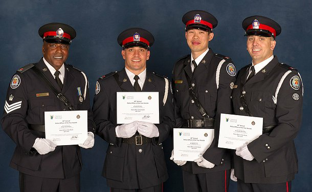 Four men in TPS uniform holding certificates