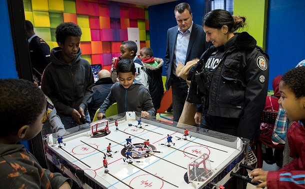 A woman in TPS uniform watches kids play table hockey