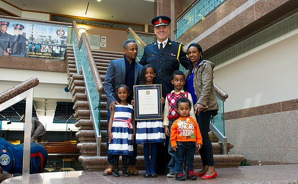 An 8-year-old girl with three young siblings all under six, standing with her mother, father and the police Chief.